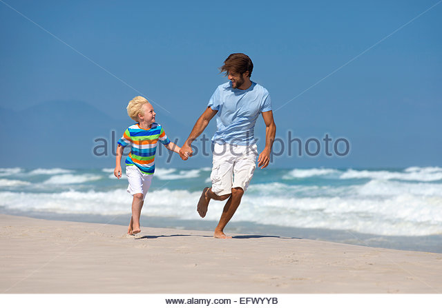 Happy Father and son, holding hands, running on sunny beach - Stock Image
