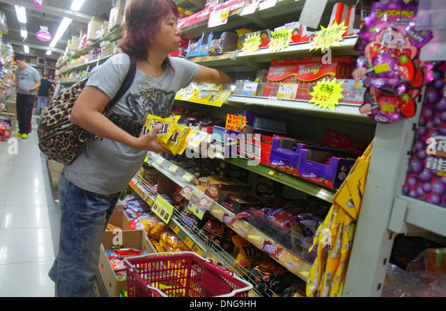 Hong Kong China Kowloon Sham Shui Po shopping grocery store supermarket sale display shelves Asian woman candy - Stock Image