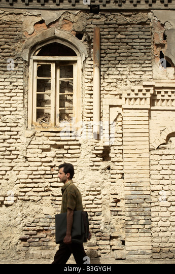 A man walking in front of an old derelict house near the Grand Bazaar of Tehran - Stock Image