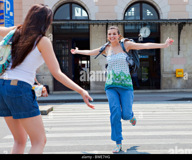 Young women meeting at train station - Stock Image
