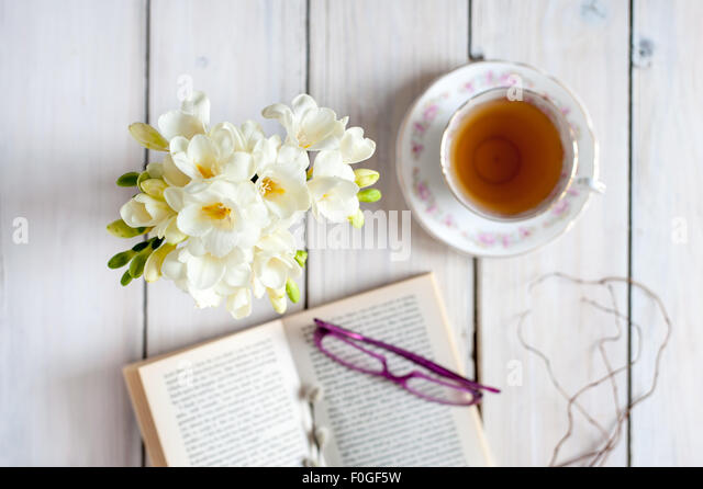 closeup of white freesias on blue placemat with blurred vintage teacup and saucer in the background, on rustic wooden - Stock Image