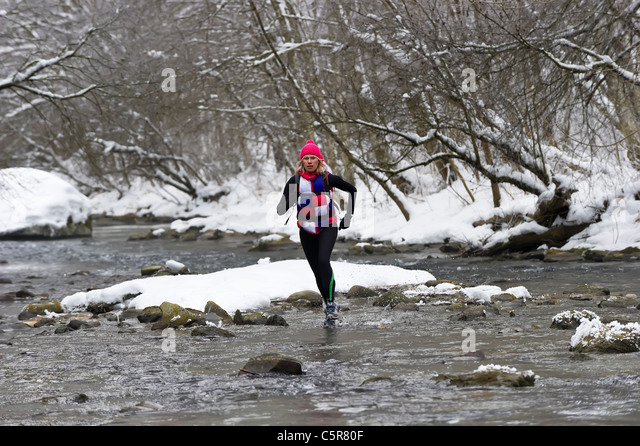 A jogger crossing a snowy river. - Stock-Bilder