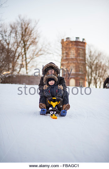 Finland, Usimaa, Helsinki, Sinebrychoffin puisto, Mother and son (4-5) on sled - Stock Image