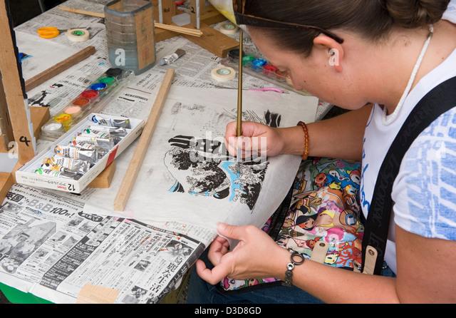 Non-Japanese female foreigner has a hand at painting a copy of old Ukiyo-e woodblock print at fair in Odawara, Kanagawa, - Stock Image
