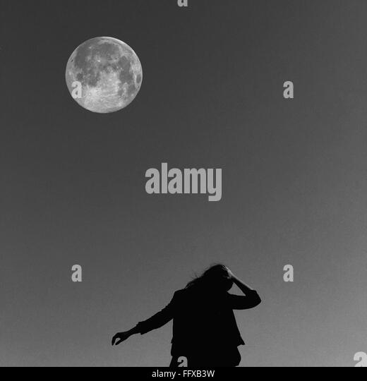 Low Angle View Of Woman Against The Moon - Stock Image