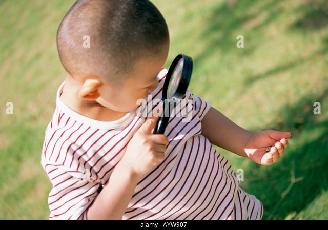 Boy looking into magnifying glass - Stock-Bilder