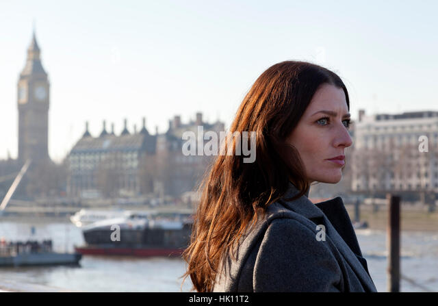 An attractive dark haired woman with pale complexion walks while carrying a business case - Stock Image