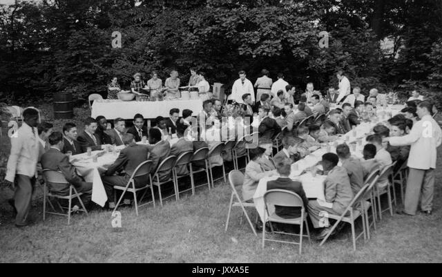 Full length landscape shot of young boys seated around dinner tables outdoors, some African American; Dobbs Ferry, - Stock Image