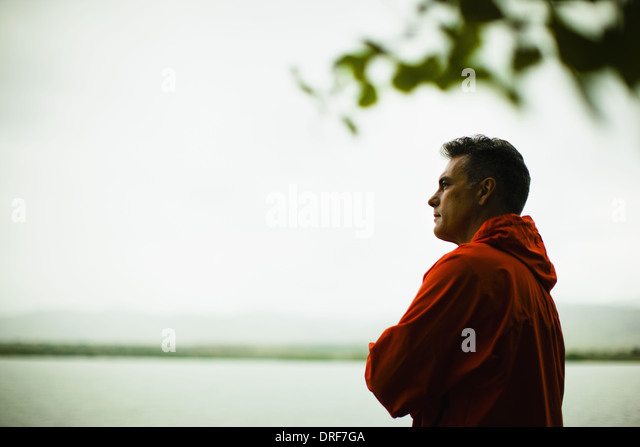Colorado USA middle aged man red jacket deep in thought - Stock Image