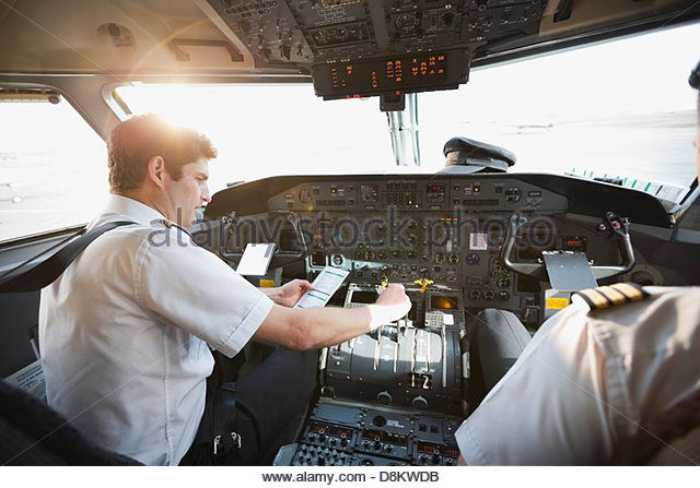 Pilot and co-pilot checking control panel in airplane cockpit - Stock Image