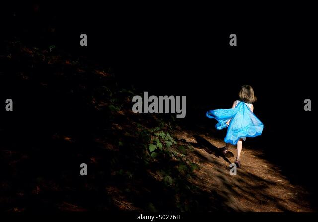 A little girl runs through the forest in a fairy costume. - Stock Image