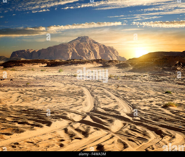 Rocks in sand desert in sunny evening - Stock Image