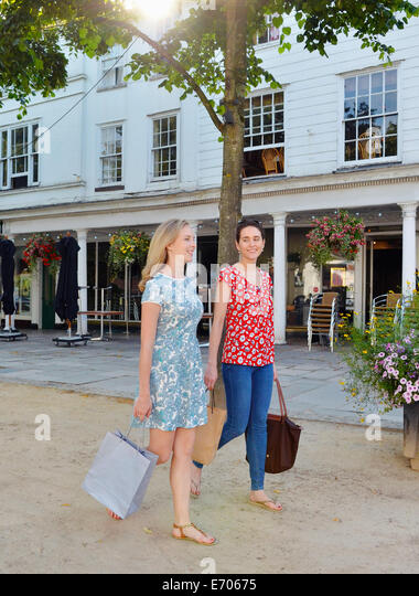 Two young women strolling along street carrying shopping bags - Stock Image