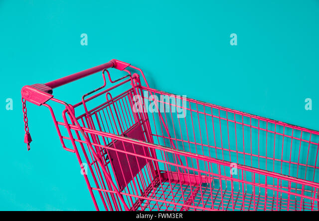 Pink Shopping Cart Against Colored Background - Stock Image