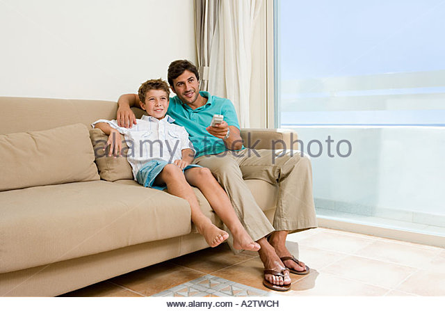 Father and son sitting on sofa - Stock Image