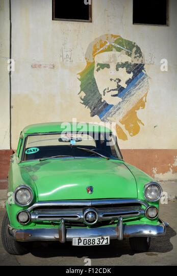 Vintage Green Ford taxi parked beneath Che Guevara mural in the parking lot in Old Havana Cuba - Stock Image