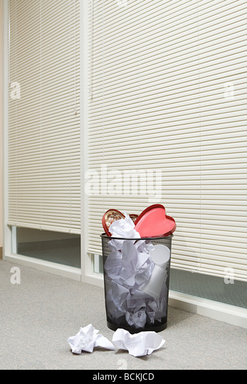 Office wastepaper basket full of paper and discarded valentines chocolate box - Stock Image