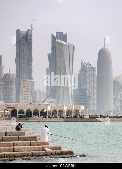 Men fishing on The Corniche with modern office towers and skyline in business district in Doha Qatar - Stock Image
