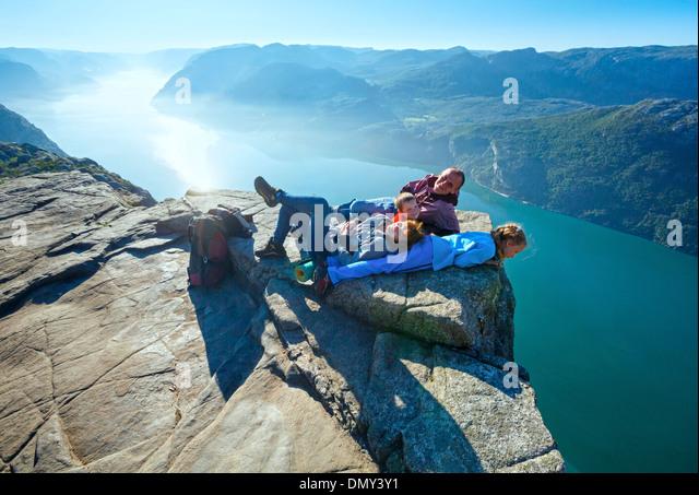 Happy family on top of Preikestolen massive cliff (Norway, Lysefjorden summer view) - Stock-Bilder