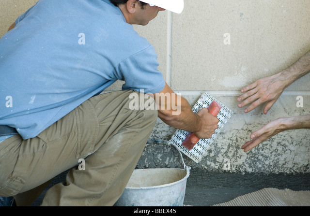 Mason receving guidance on proper masonry technique - Stock Image