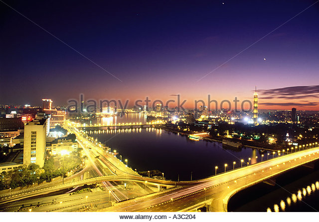 View of bridges crossing the Nile River and the Cairo skyline at night Cairo Egypt - Stock Image