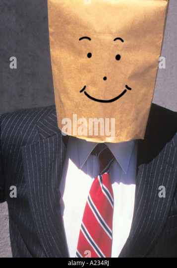 Businessman With Brown Paper Bag Over His Head Smiling - Stock Image