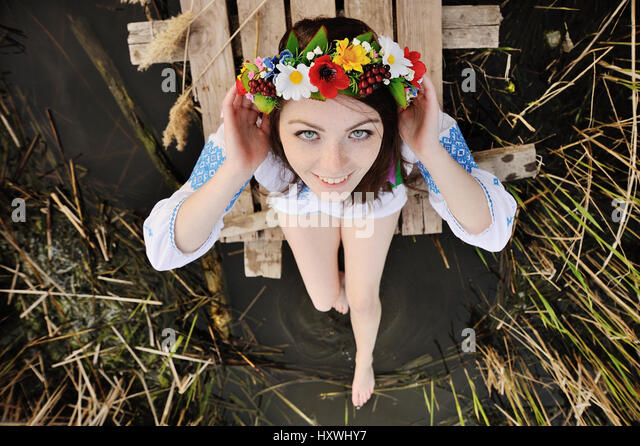 girl in a flower wreath on his head sitting on the bridge and we - Stock Image