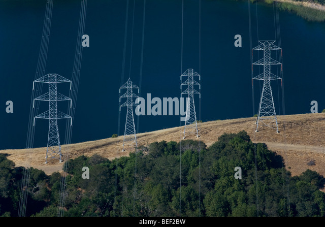 aerial view above power transmission lines towers at California reservoir - Stock Image