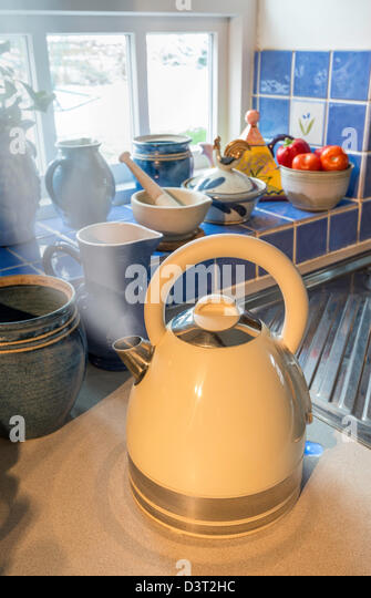 BOILING KETTLE WITH STEAM COMING FROM SPOUT IN COUNTRY KITCHEN UK - Stock Image