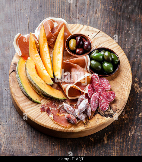 Antipasto snack ham, melon and olives on wooden background - Stock Image