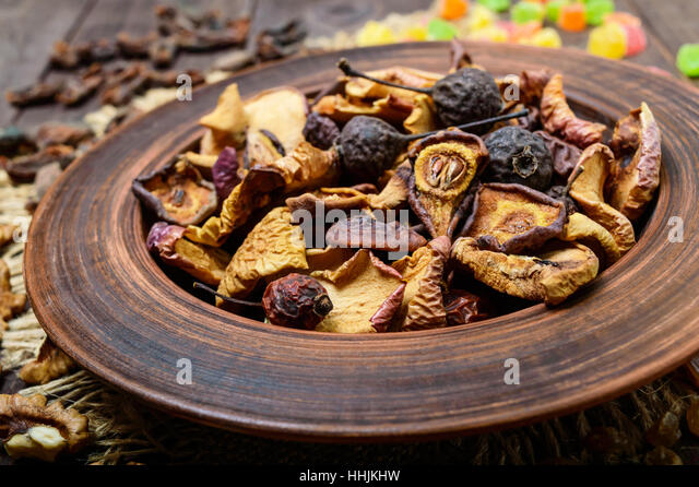 Dried fruit (apples, pears, apricots), berries, raisins and nuts in a bowl on dark wooden background. Close up. - Stock Image