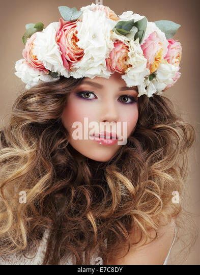 Romantic Woman in Wreath of Flowers with Perfect Skin and Frizzy Hair - Stock Image