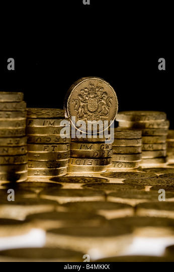 Piles of pound coins with black background - Stock Image