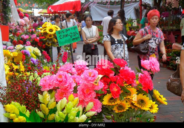 Singapore Bugis Waterloo Street shopping Asian woman flowers display for sale - Stock Image