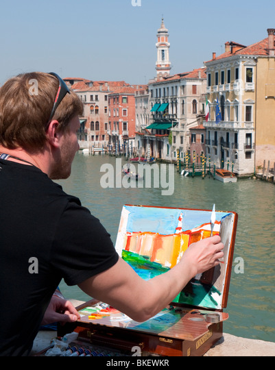 Artist painting scene beside Grand Canal in Venice - Stock Image