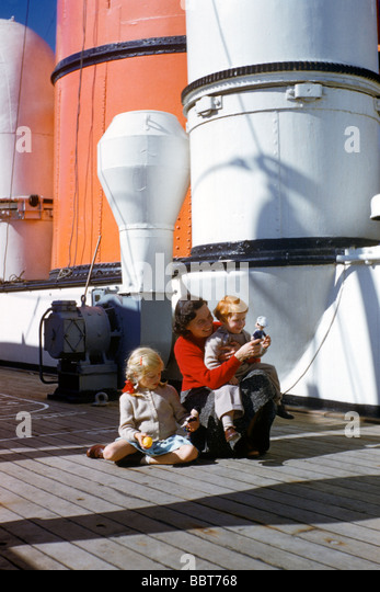 Young family on boat deck , emigrating to New Life in North America 1955 - Stock Image