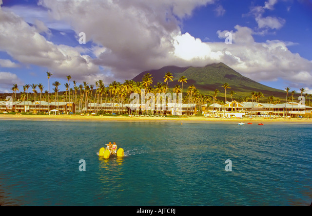 Nevis, Caribbean, couple on water bike in front of Four Seasons Resort with Mount Nevis in background - Stock Image