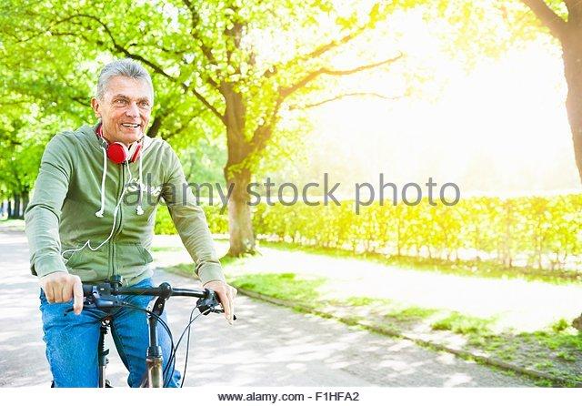 Senior man riding bicycle, looking away, copy space - Stock Image