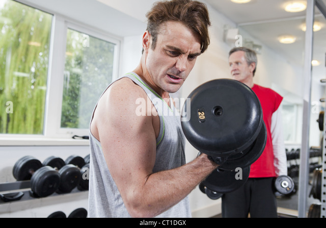 Man lifting weights in gym - Stock Image