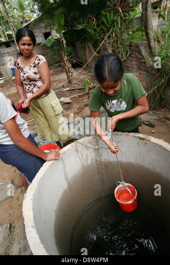 Young girl drawing water from a well in the garden of her house as her sisters watch, Beruwela, Sri Lanka - Stock Image