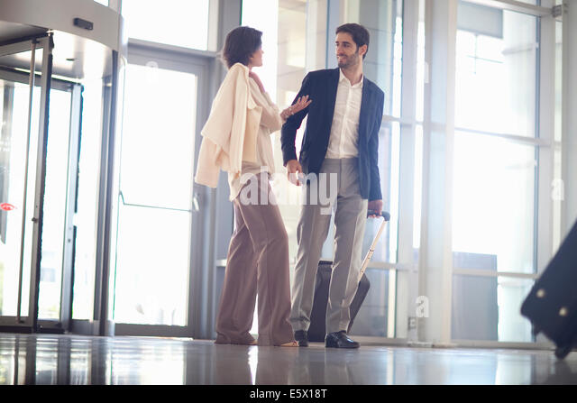 Young businesswoman and businessman arriving at conference centre - Stock Image