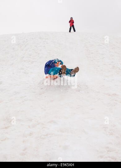 small boy sledging fast down a steep hill with small girl standing at top of hill in background - Stock Image