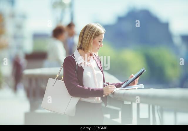 Businesswoman using digital tablet at urban waterfront - Stock Image
