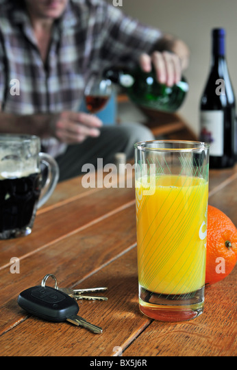 Car key, drunken man pouring wine, alcoholic drinks and soft drink on table to illustrate responsible driving - Stock Image