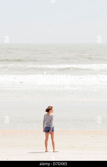 Girl looking at beach - Stock Image
