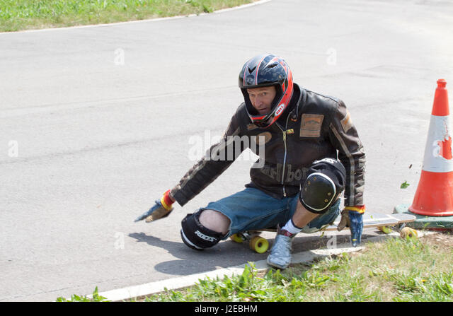 Downhill skateboarder looks at the camera having slid off the road - Stock Image