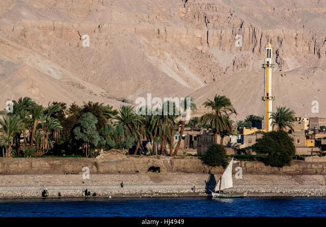 Life along the Nile River in Egypt with a minaret and sailboat - Stock-Bilder