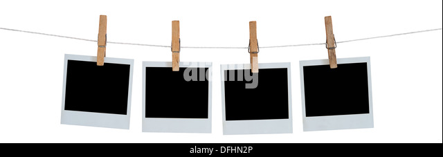 Blank Polaroid photographs hanging on a line - Stock Image
