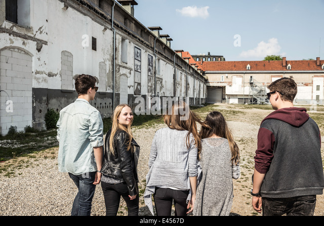 Teenagers strolling past abandoned buildings - Stock-Bilder