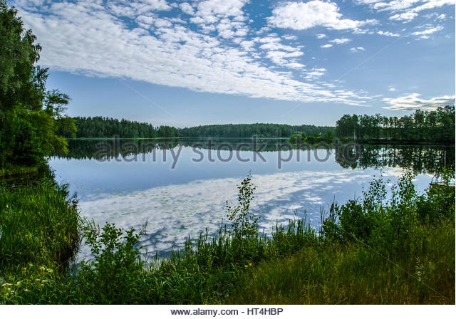 Reflections of clouds in summer blue water, Scandinavia. - Stock Image